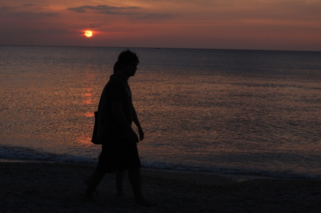 A couple walks across the silky soft sand at gloaming on Koh Lanta, one of many serene Thai islands.