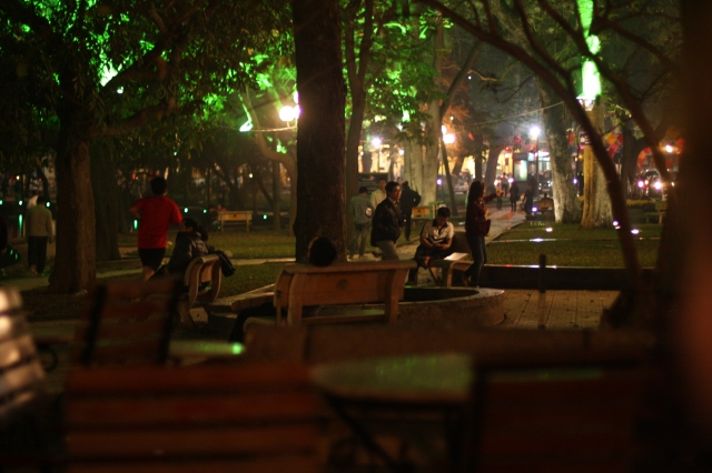 Illuminated at night, this Ha Noi park bustles with activity, capturing HaNoi's locals carrying on with a part of their everyday routine.