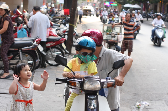A father speaks to his gesticulating daughter before setting off with his son, whose mask protects him from Ho Chi Minh's severe pollution.