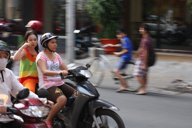 Savouring every morsel of her tantalising ice cream treat, this young Vietnamese makes the most of her afternoon scooter commute.