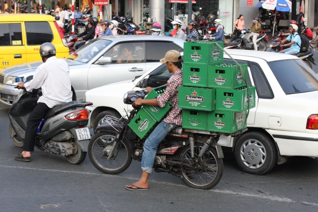 Like an ant carrying a load well in excess of his own body weight, this Ho Chi Minh resident transports nine crates of Heineken, a stack of sweet nectar worth its weight in gold.